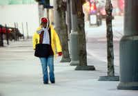 A woman walks Tuesday morning along Pacific Avenue in downtown Dallas.