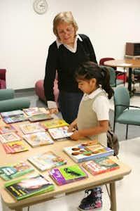 Volunteer Cheryl Alexander helps Stark student Maria Jose, 6, to select books to read with her volunteer helper.Photo by RUTH HAESEMEYER