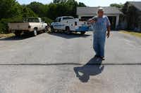 Joe Hardman stands at the line he spray painted to visualize how much of his driveway he will lose after the city expands his street into a divided four-lane road, taking over 6,000 square feet of his property.