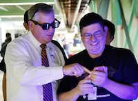 TI exec Greg Delagi (left) admired his new look — dress shirt, tie and LED shades — in a picture taken by do-it-yourselfer Roberto Rivera-Sandoval.Tom Fox - Staff Photographer