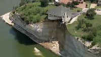 On Thursday, the house teetered on a cliff about 75 feet above Lake Whitney.WFAA.com  -