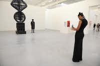 """Erika Oliver takes a photo of Charles Smith II next to """"Elliptic Umbilic/Fait Accompli"""" by Sterling Ruby during a public tour at The Warehouse.Photo by ROSE BACA - neighborsgo staff photographer"""