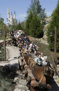 The new Seven Dwarfs Mine Train roller coaster in Disney World plunges through a mountainous landscape.John Raoux  -  The Associated Press