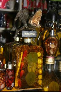 In this June 7, 2013 photo, a dried reptile sits on a bottle of natural perfume at Maria Rios' stand at the witches market in Lima, Peru. Rios, originally from Iquitos in the Amazon jungle, has been making these herbal perfumes based on an ancient recipe, for 25 years. Her perfumes are alleged to attract money, find true love or ensure health.