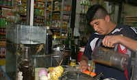 In this June 7, 2013 photo, Mario Lopez pours a freshly mixed folk cure into a strainer at his stand inside the witches market in Lima, Peru. The mixture is made from live frogs, left in tank. The drink is purported to cure respiratory problems, impotence, anemia and work as an aphrodesiac.