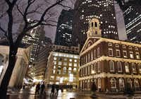 In this Feb. 22, 2007 file photo, Faneuil Hall, right, is seen at night among the buildings in downtown in Boston. Faneuil Hall is one of the historic sites on Boston's Freedom Trail.
