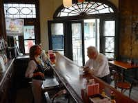 In this March 25, 2013 photo, bartender Jennifer M. Giannobile serves Louis Ferry at the iconic New Orleans restaurant Tujague's in the French Quarter.