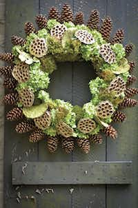 A radiating rim of pine cones with lotus pods, preserved tree fungi, hydrangeas and moss form a spectacular wreath by James T. Farmer III lthat looks like a sunburst. $155 at jamesfarmer.com.