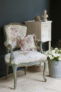 Annie Sloan's grayed colors are used on the walls, table and chair, which is upholstered in her Faded Roses fabric.