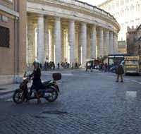 Knight gets around Rome on a Honda scooter, like the locals. The colonnade in the background is part of St. Peter's Square. It serves as the international border between the Vatican City and Rome.