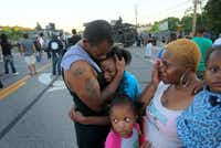 """I'm out here to stand for my children and their future,"" said Terrell Williams El, who is hugging his daughter Sharell, 9, while standing with his wife, Shamika Williams, and daughters Tamika, 6, and Sharell, 2, near the QuickTrip at 9240 W. Florissant Ave. in Ferguson, Mo., on Wednesday, Aug. 13, 2014. (David Carson/St. Louis Post-Dispatch/MCT)David Carson - MCT"