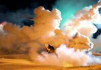 A protester takes shelter from the tear gas exploding around him in Ferguson, Mo., on Wednesday, Aug. 13, 2014. It was the fourth night of unrest in Ferguson after the fatal police shooting of a teen on Saturday. (David Carson/St. Louis Post-Dispatch/MCT)David Carson - MCT