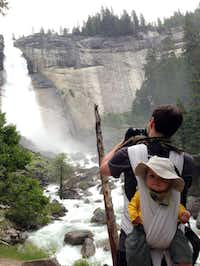 A hiker photographs Nevada Falls along the Mist Trail in Yosemite National Park with baby on his back, June 4, 2013.