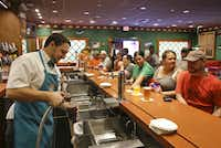 """In this Sept. 5, 2013 photo, Lee Phillips, left, serves up a Buzz Cola at """"The Simpson's"""" themed Moe's Tavern at Springfield USA at Universal Orlando in Orlando, Fla. In addition to the cola customers can order other beverages such as a Duff Beer or a non-alcoholic Flaming Moe."""