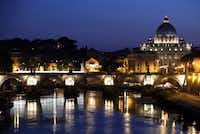 St. Peter's Basilica in Vatican City is seen illuminated at night beyond St. Angelo's bridge, from the banks of the Tiber river in Rome, Italy.