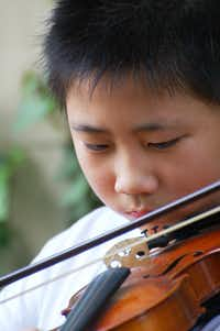 Bohan Zhang, then 12, practicing the violin outside his apartment building in Dallas.