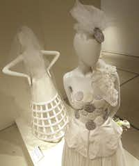 A 1994 dress by Victor Costa (left) is displayed with a 2011 by Zigwai Remy Ddukomaiya.LM Otero  -  The Associated Press