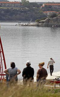 Friends of  Jacob Logan's mother -- Christie Candelas (left) and Nancy Gergas (right) and another co-worker stood watch as crews searched for Jacob Logan at Possum Kingdom Lake on Monday.
