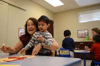 Maria Stacy, Spanish translator, helps Oscar Leon work on an art project during the Bridge Group class, with children ages 32 to 35 months, in the Early Childhood Intervention program at the Warren Center.Rose Baca  -  neighborsgo staff photographer