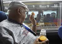 DeLuca waves to a youngster from his seat on the retiree bus that transported him and 50 other former NASA employees to view the final shuttle launch in Florida on July 8.