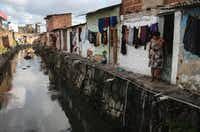 RECIFE, BRAZIL - MAY 31: A woman stands in front of her home along a polluted canal on May 31, 2016 in Recife, Brazil. Lack of proper drainage in areas is one of many contributing factors leading to mosquito-borne illnesses in the city, including the Zika virus. Microcephaly is a birth defect linked to the Zika virus where infants are born with abnormally small heads. The city of Recife and surrounding Pernambuco state remain the epicenter of the Zika virus outbreak, which has now spread to many countries in the Americas. A group of health experts recently called for the Rio 2016 Olympic Games to be postponed or cancelled due to the Zika threat but the WHO (World Health Organization) rejected the proposal. (Photo by Mario Tama/Getty Images)