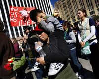 Micaela Steiner carried John Moses Gallardo, 4, on her shoulders during the march from Cathedral Guadalupe to the Earle Cabell Federal Courthouse