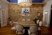 A stone wall provides a dramatic backdrop for the dining room upstairs at  Consuela's new Austin headquarters.