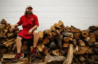 Stiles Switch BBQ & Brew pitmaster Lance Kirkpatrick poses for a photo on his oak wood pile out back of the restaurant on N. Lamar in Austin.