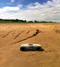 An old boombox plays no more on what is now a beach area since the water receded at Lake Bridgeport. Long-term trends point to the likelihood of warmer, drier weather for the next 10 to 15 years, experts say.