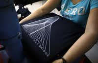 Isabel Rodriquez prepares to print the image of the Margaret Hunt Hill Bridge on the front of a T-shirt at Classic Caps and Embroidery in Dallas. One filmmaker says the bridge may become Dallas' next popular filming location.