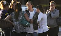 A group of friends are overcome with emotion as they gather outside Gateway High School, Friday July 20, 2012, in Aurora, Colo. They recieved news that their friend was killed during a shooting early Friday inside the Aurora movie theater.
