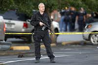 A SWAT team officer stands watch near an apartment house where the suspect in a shooting at a movie theatre lived in Aurora, Colo., Friday, July 20, 2012.