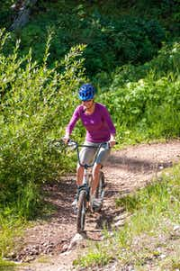 A woman tackles Purgatory's Diggler trail.  Like top-end mountain bikes, these scooters feature knobby tires and disc brakes.