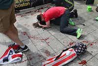 A man tries to comfort a victim near the scene of the first explosion near the finish line of the Boston Marathon.John Tlumacki - The Boston Globe
