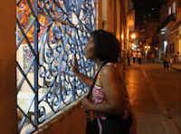 Credo Choir member Mattie Jette peers at the art in a Havana storefront.Joy Tipping  -  Staff
