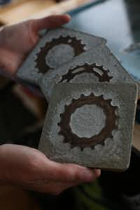 Rachel Spire holds coasters made of bicycle parts at her house in Grapevine October 16, 2012.