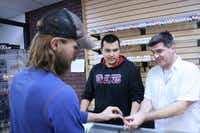 Frank Malara (right), owner of The Vapor Zone, helps Lewisville resident Max Gaebler select from an assortment of e-cigarette products. Malara's store specializes in e-cigarettes, which have been the subject of three area ordinances in Lewisville, Flower Mound and Highland Village banning sale of the devices to minors.Staff photos by DANIEL HOUSTON