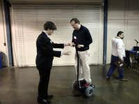 """Electrical engineer Paul Hylander, right, rides a version of a Segway designed by Bishop Lynch student Matthew Whitby, 16, called a yaryar, which means """"smaller"""" in Somali, according to Whitby, during the 2014 Dallas Regional Science and Engineering Fair at Fair Park in Dallas. Whitby's version, which is smaller and lighter than a similar Segway, totaled a cost of $650 to build, whlie a similar Segway costs over $6,000 to purchase."""