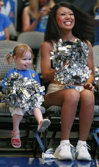 Mavericks Dancer Natsuki Kaito, right, sits with two-year-old Sevyn Tennison as they get ready to watch the game during the watch party at the American Airlines Center in Dallas for Game Six of the NBA Finals between the Dallas Mavericks and the Miami Heat in Miami on Sunday, June 12, 2011.
