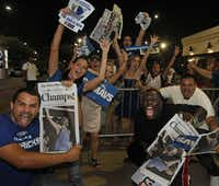 Fans celebrate with editions of the Dallas Morning News outside the arena after the Mavs beat the Miami, at the watch party at the American Airlines Center in Dallas for Game Six of the NBA Finals between the Dallas Mavericks and the Miami Heat in Miami on Sunday, June 12, 2011.