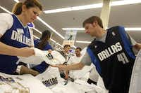 Academy Sports + Outdoors employee, Suela Bashllari, continues to organize the remaining merchandise as Mavs fan, Matt Clark, makes his selection at the store on Forest Lane in Dallas, Texas on June 12, 2011.