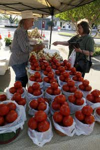 Roger Heddin of the Mill Creek Farm in Canton, Texas, helps a customer at the Rockwall Farmers Market  in Rockwall, Texas, Saturday, May 7, 2011. (Ron Heflin/Special Contributor)