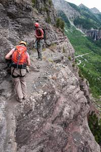 Guide Joe Eppler watches as Dianne Leeth unclips from a narrow section of Telluride's Via Ferrata.  The steel cables allow inexperienced climbers to enjoy some of the same sights and thrills as accomplished rock climbers.