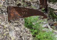 A rusty arrow gives an artful warning that climbers may occupy the rocks below.  The cliffs below the Via Ferrata have long been a favorite of local rock climbers.
