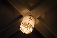 A vintage light fixture bearing the symbol of a cross hangs in the now-defunct Trinity Presbyterian Church building.
