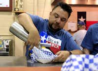 Abel Gonzales puts whipped cream on Awesome Deep Fried Nutella during the Big Tex Choice Awards.