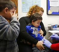 Six-year-old Errmer Rolon couldn't watch as his little brother Bayron Rolon got a flu shot. The boys' mother, Glendalee Rolon, took them to the clinic on Thursday.