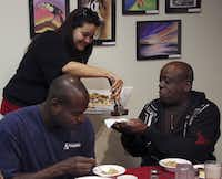 Volunteer Arzoo Vasaya, standing left, offers pastries to guests James McCain (left) and Orlando Dodd at the free breakfast for the at the Cathedral of Hope Saturday November 17, 2012.