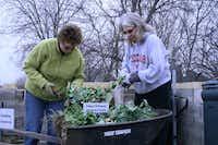 Lisa Ingalls (left) and Terri Barrett add to The Giving Garden's compost pile.Staff photo by ELIZABETH KNIGHTEN - Neighborsgo