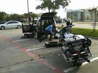 Garland Police Officer R.P. Clark reaches beneath the sport utility vehicle to loosen the gas tank in attempts to free a kitten.